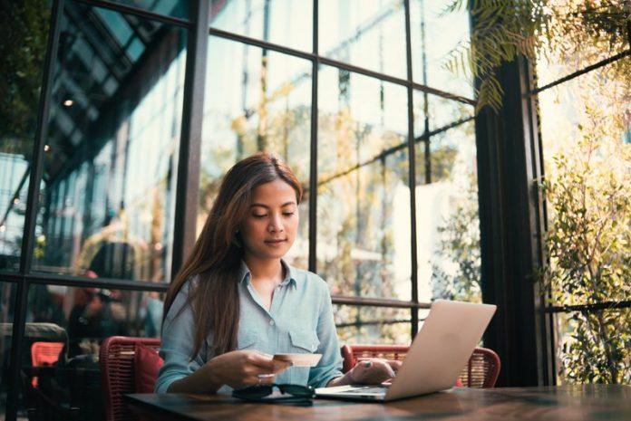Młoda kobieta używająca karty tradycyjnej zamiast karty wirtualnej